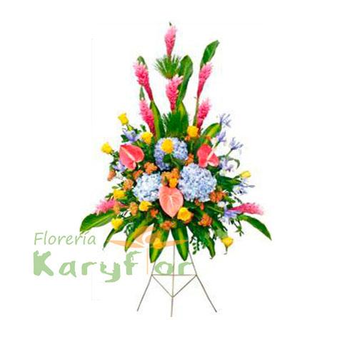 Arreglo floral compuesto por finas rosas, hortencias, anturios, ginger, iris, variedad de flores, palmeras y fino follaje elaborado en tripode. Incluye tarjeta de dedicatoria