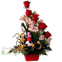 Arreglo floral elaborado con 5 rosas, verónicas, astromélias y fino follaje en base de cerámica decorada. Incluye tarjeta dedicatoria Pueden agregar adicionales ingresando a opción REGALOS.
