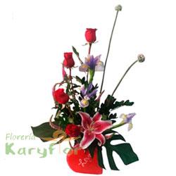 Arreglo floral elaborado con 4 rosas, iris azul, verónicas y fino follaje en base de cerámica corazón (con escritura LOVE). Incluye tarjeta dedicatoria.