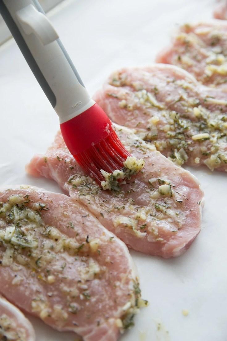 boneless thin pork chops on a sheet pan with a baster adding seasoning