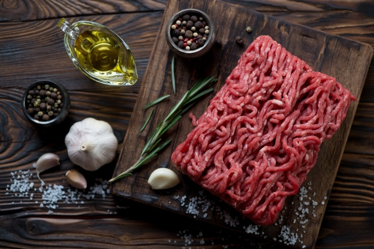 cutting board with raw ground beef on it along with spices for keto meal prep