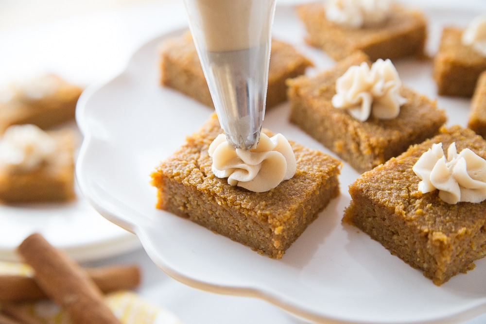 Keto Pumpkin Pie Bars on a cake dish with piping bag adding cream cheese icing to the top