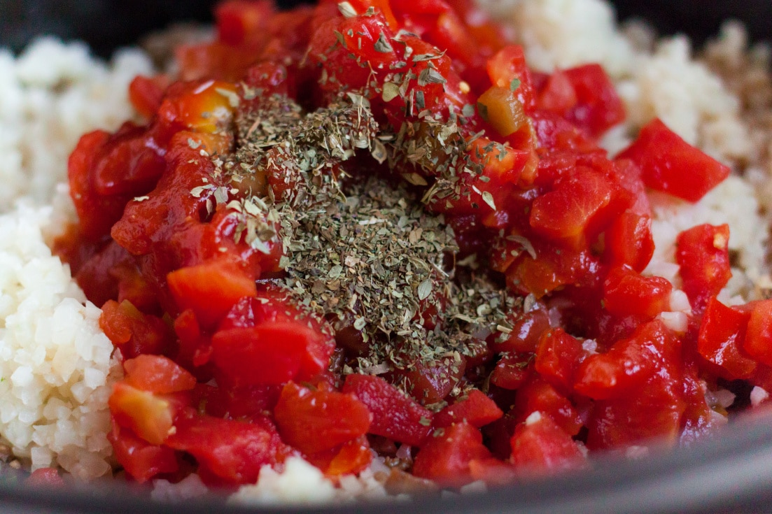 Riced cauliflower, tomatoes, and seasoning sauteing in a pan.