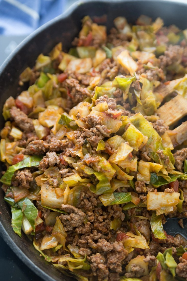 Unstuffed cabbage Rolls in a cast iron skillet with a wooden spoon stirring it