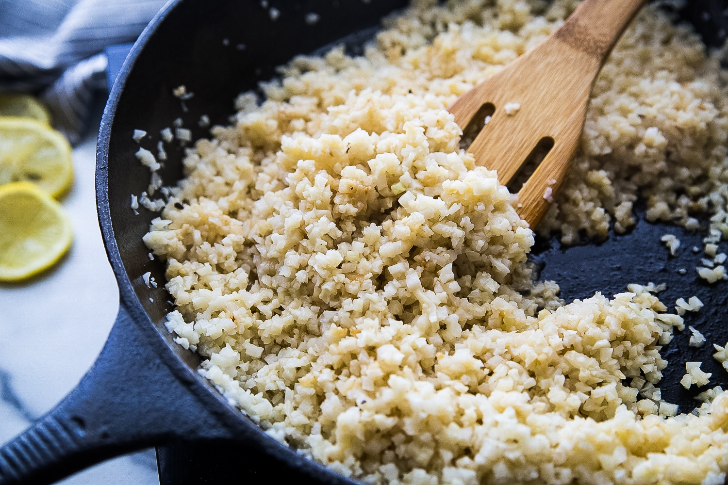 Riced cauliflower being fried in butter in a cast iron skillet.