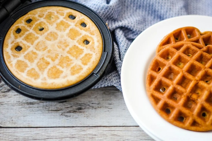 pumpkin Chaffle batter in the mini dash waffle maker with a keto waffle sitting next to it.