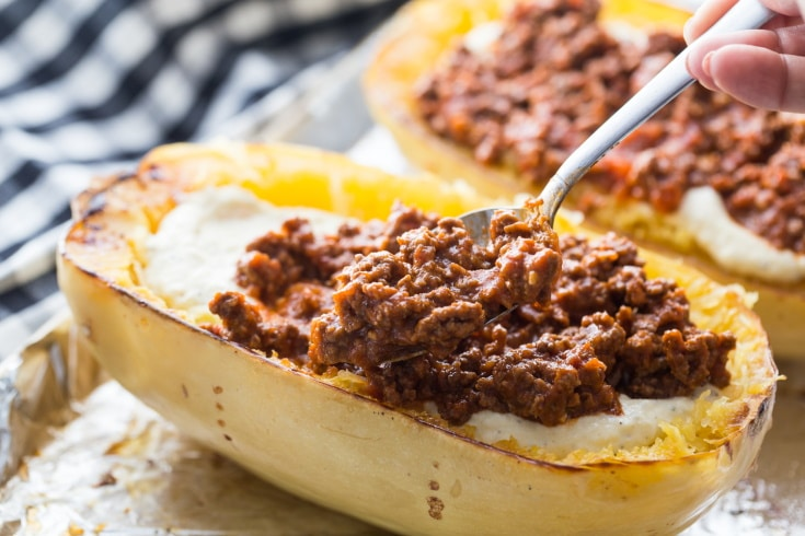 adding the low carb spaghetti sauce on top of the ricotta mixture in the spaghetti squash boats