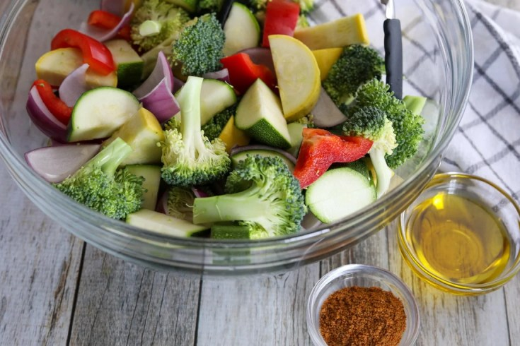 raw cut vegetables in a bowl with oil and seasoning
