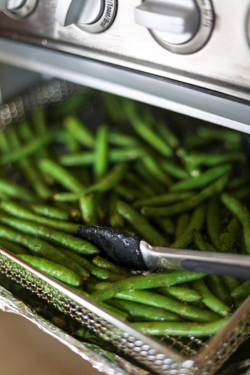 Green beans in air fryer basket with tongs.
