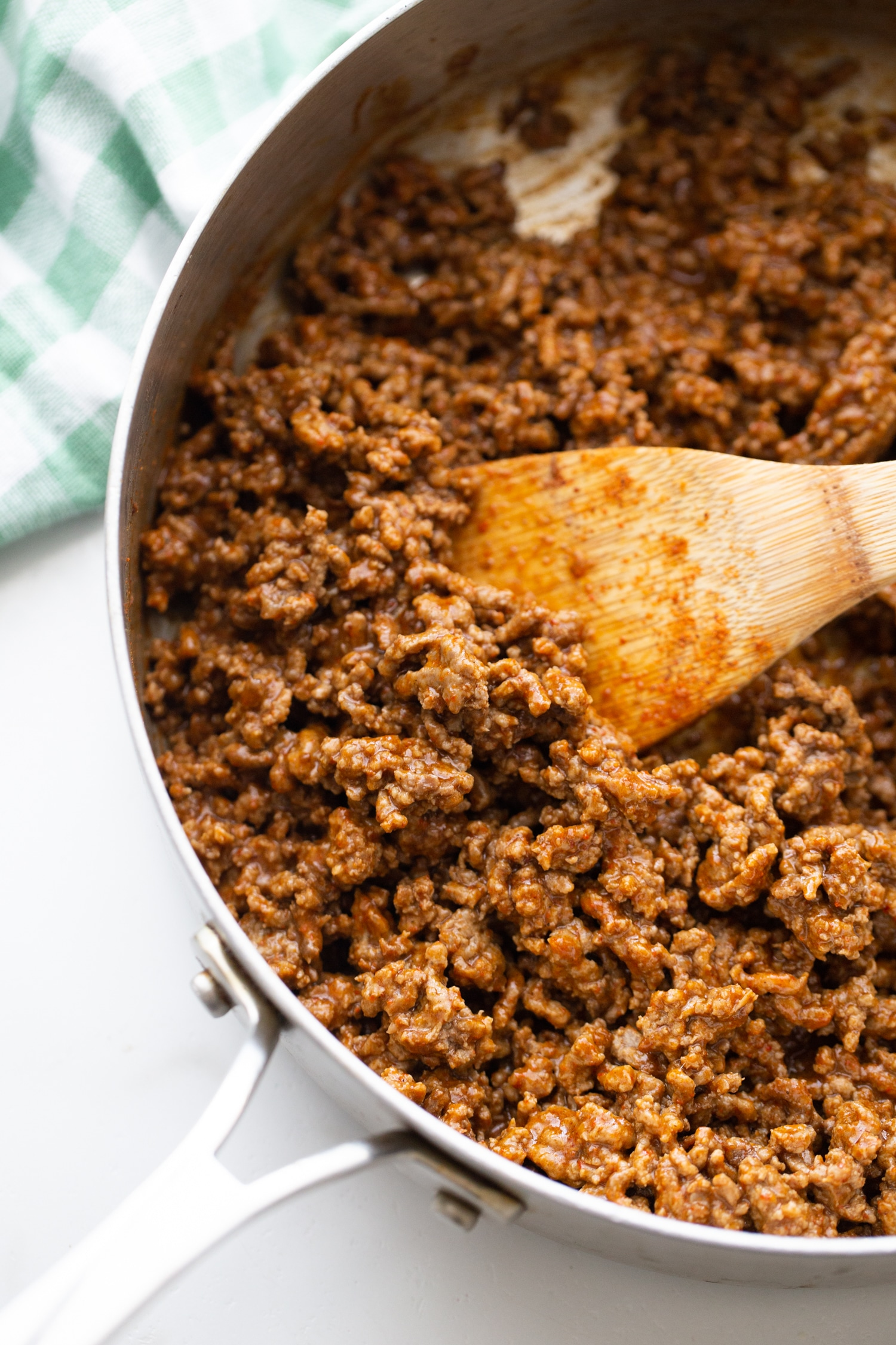 ground beef with taco seasoning sauteeing in skillet with wooden spoon