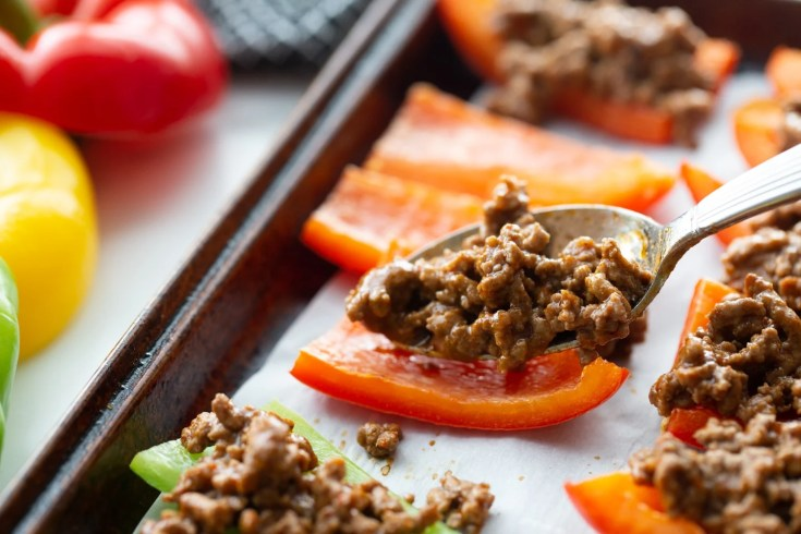 bell peppers being stuffed with ground beef mixture on baking sheet