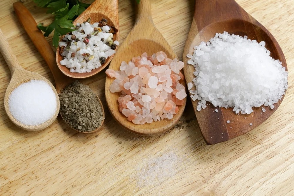 different types of salts in wooden spoons displayed on a table