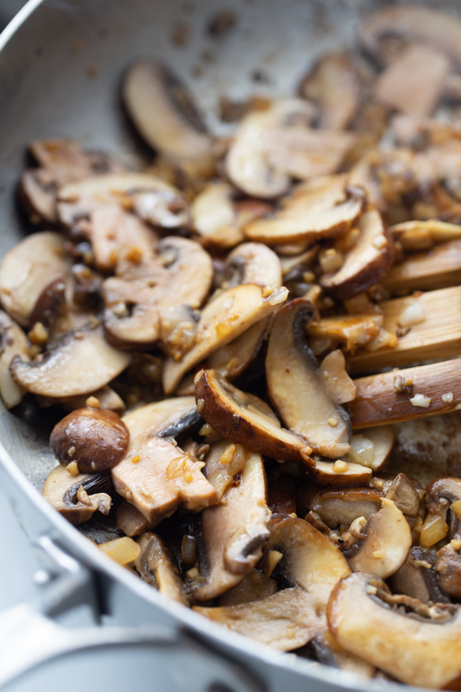 cremini mushrooms sauteeing in a skillet with onions and garlic
