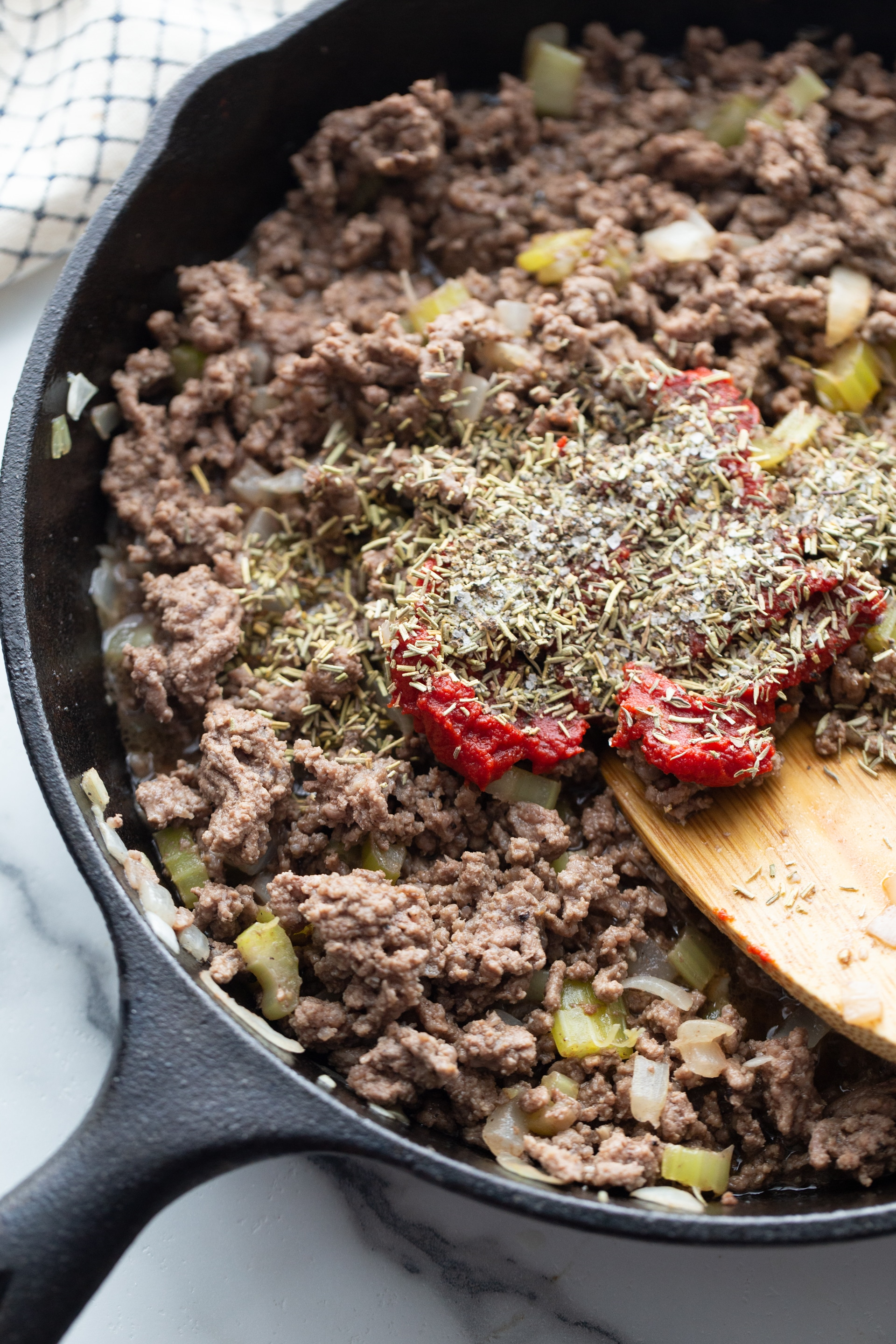 ground beef, rosemary, thyme, peppers and onions in a skillet