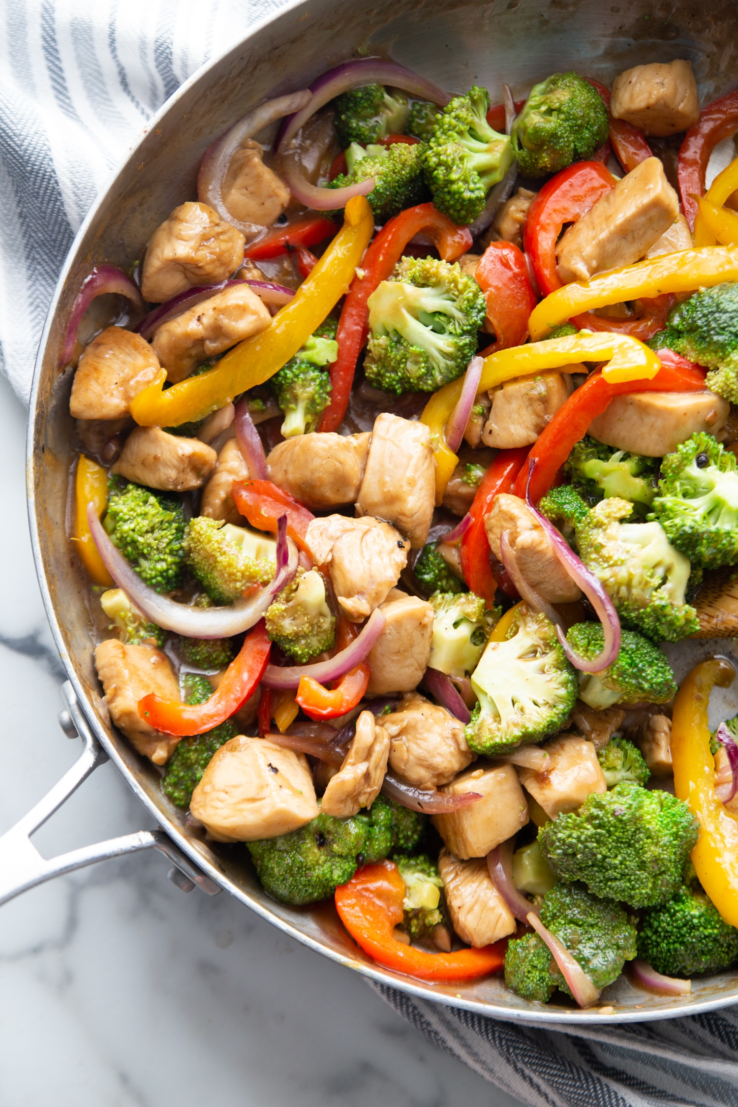 stir fry in a pan with veggies, chicken and sauce
