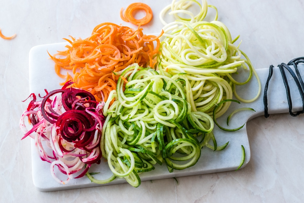 Spiralized Vegetables Noodle Carrot, Beetroot, Zucchini and Cucumber on Marble Board.
