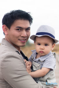 Daddy holding little boy in a fedora and overalls