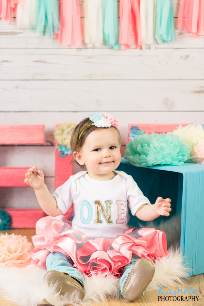 Miss Thomas' First Birthday Session: Baby wearing a pink tutu sitting on furry rug near a present and pom poms