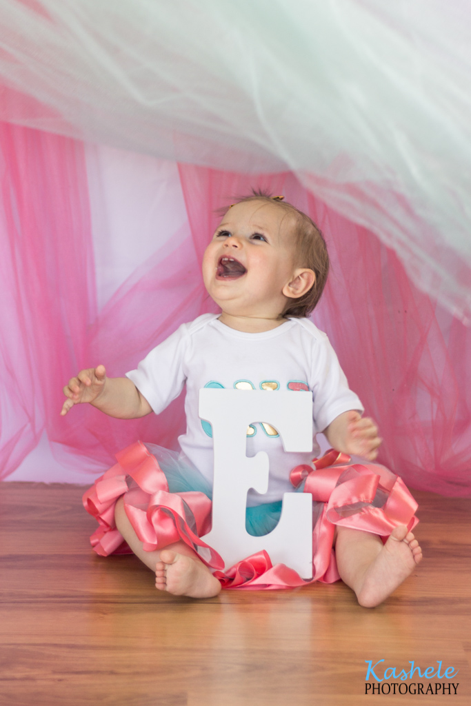 "Miss Thomas' First Birthday Session: Image of baby wearing a pink tutu holding letter ""E"" while tulle is brushed over her head"