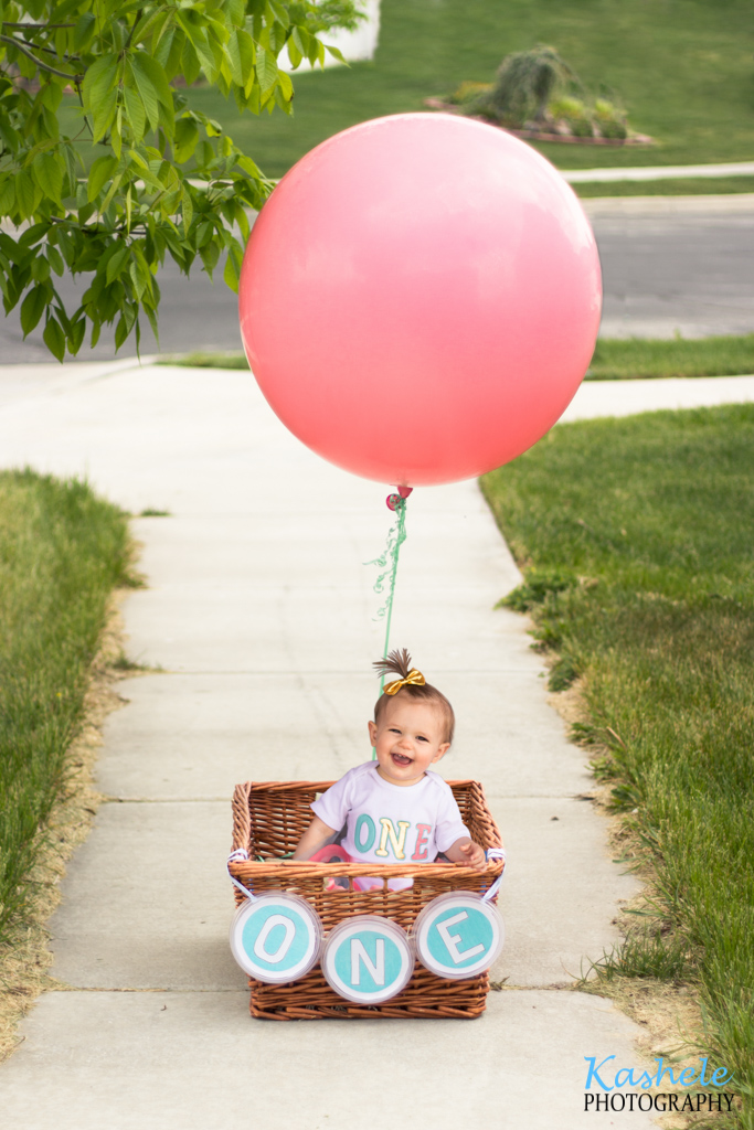 Miss Thomas' First Birthday Session: Image of baby in a basket with a big helium balloon