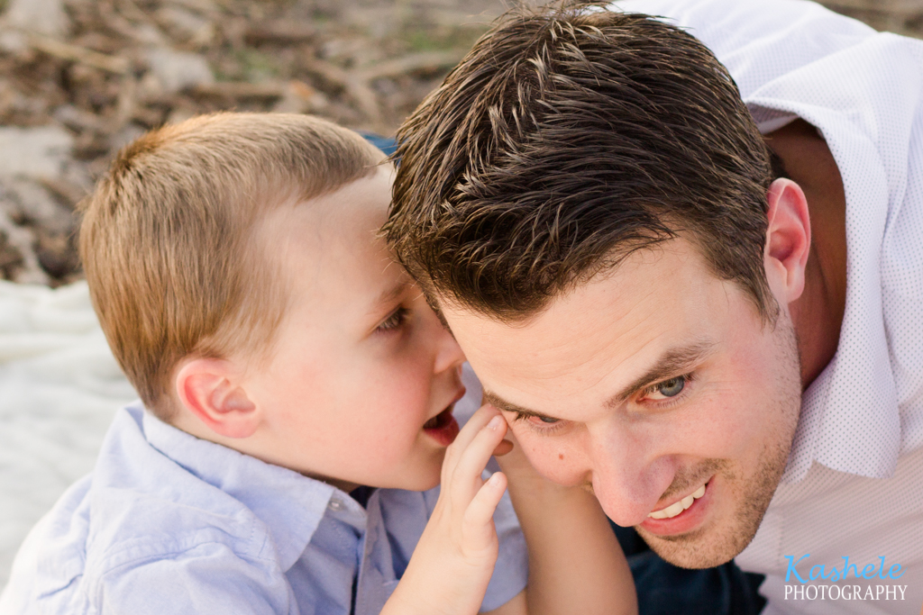 Image of the Hardy Family little boy whispering in his daddy's ear
