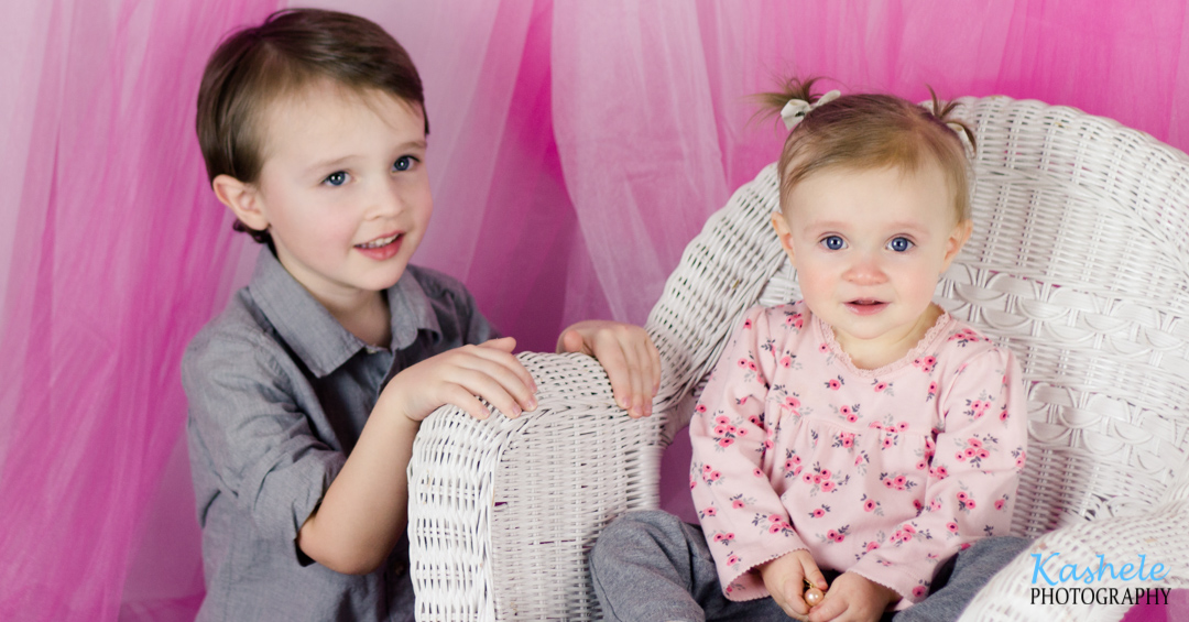 Image of brother and baby sister on a wicker chair from Miss Hardy's First Birthday Session