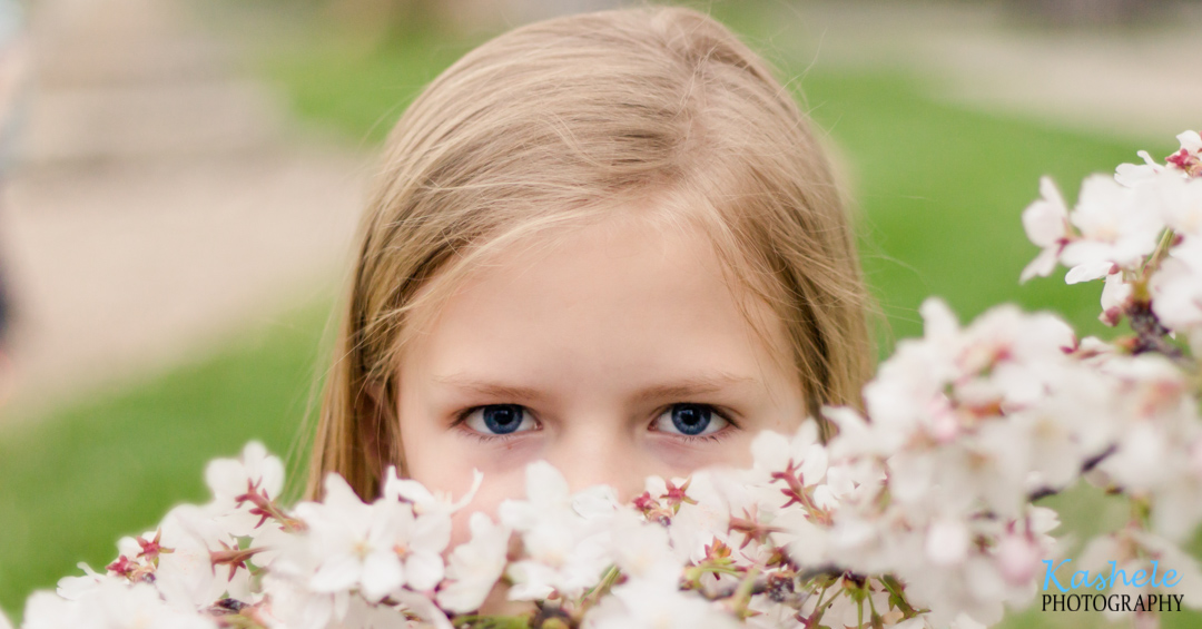 SwaLittle girl peeking over a branch of blossoms