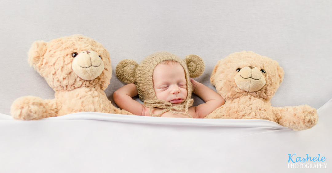 Newborn baby boy tucked into bed between teddy bears with a bear bonnet