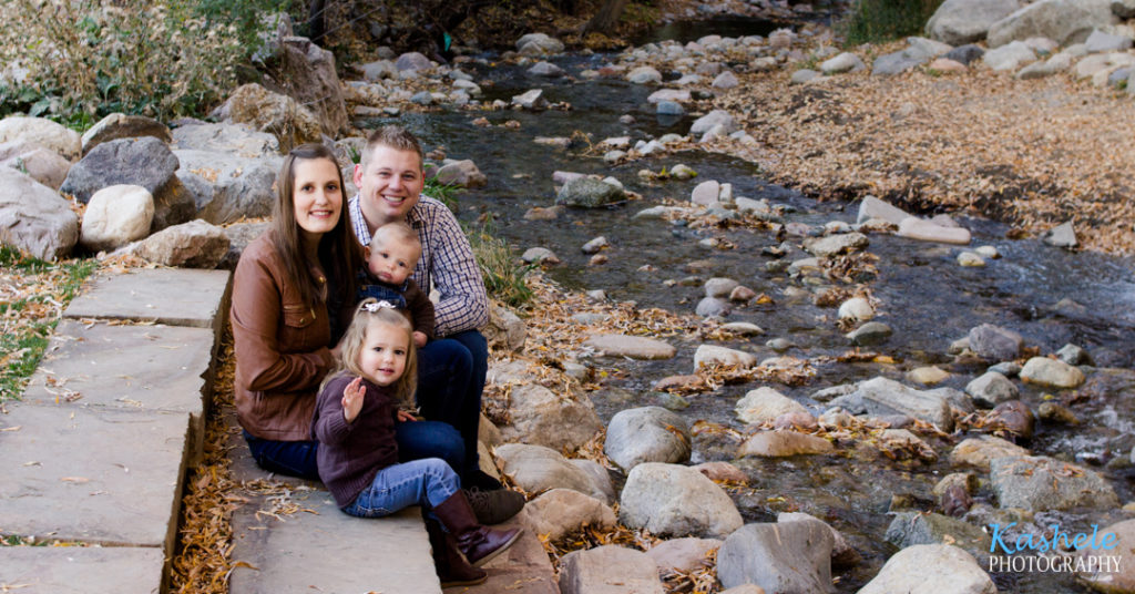 2019 Fall Family Session Thomas Family of 4 sitting on the steps beside a stream