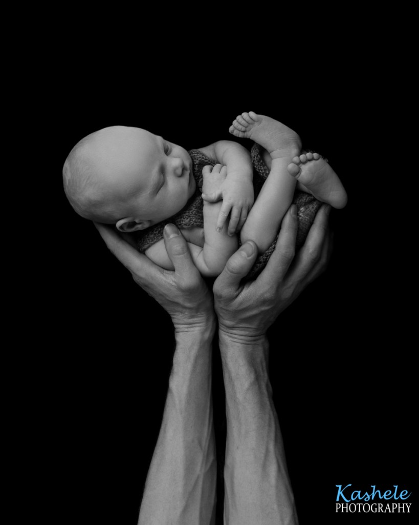 Simba pose of baby with dad's hands