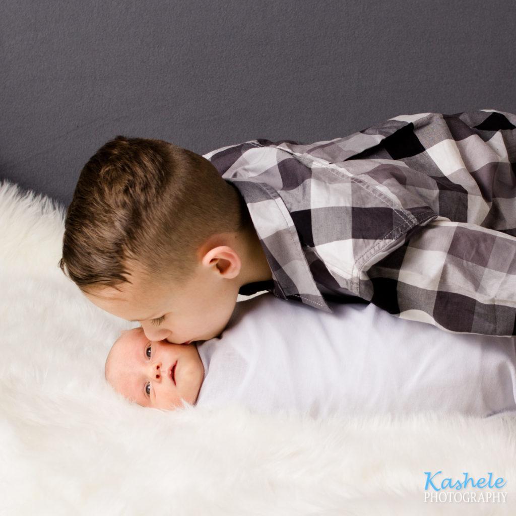 Big brother kissing baby sister