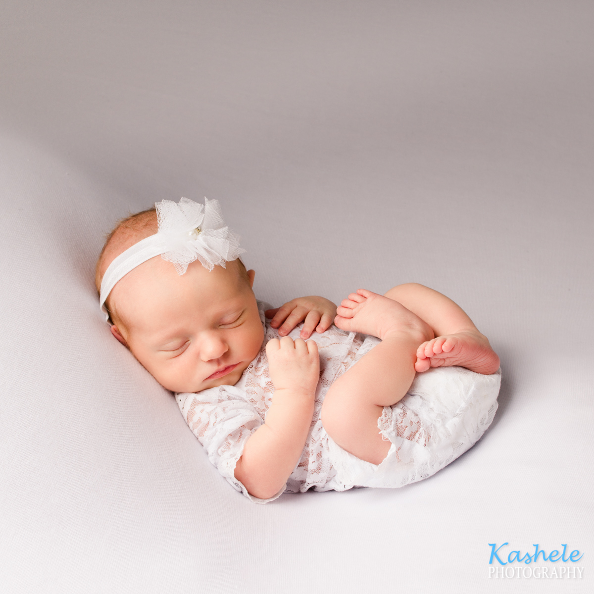 Baby in huck fin pose for utah newborn photographer post