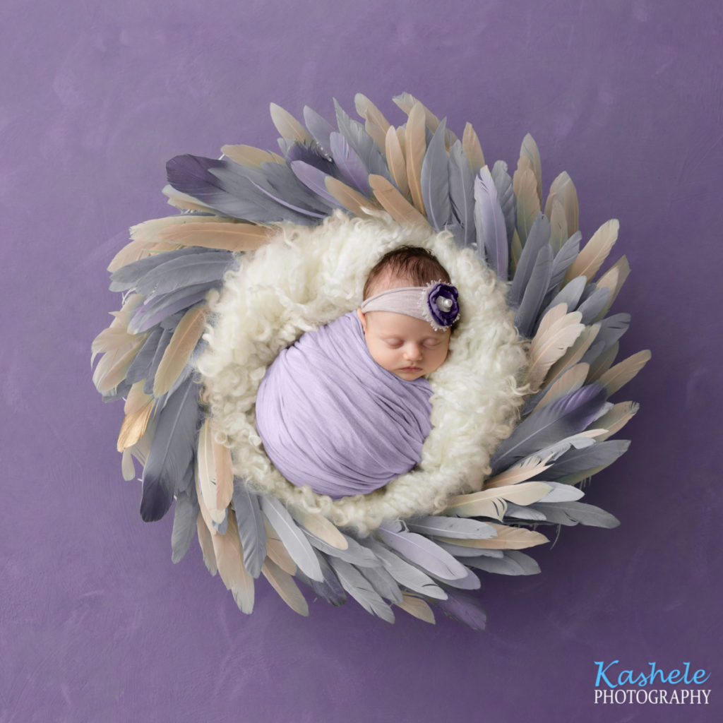 Image of baby girl in purple surrounded by curly fluff and feathers