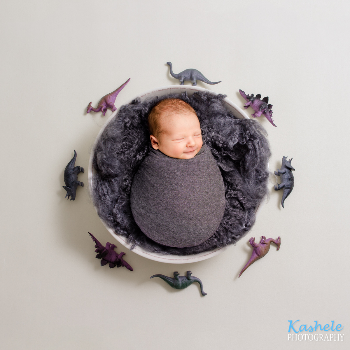 Utah Newborn Photography smiling baby in a bowl surrounded by dinosaurs