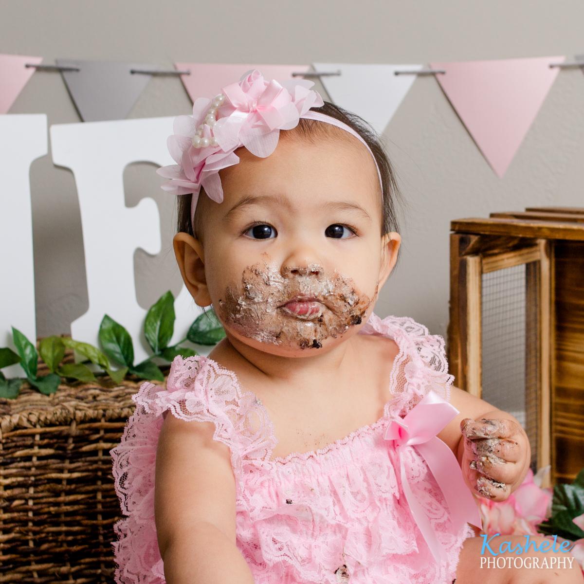 Little girl covered in cake