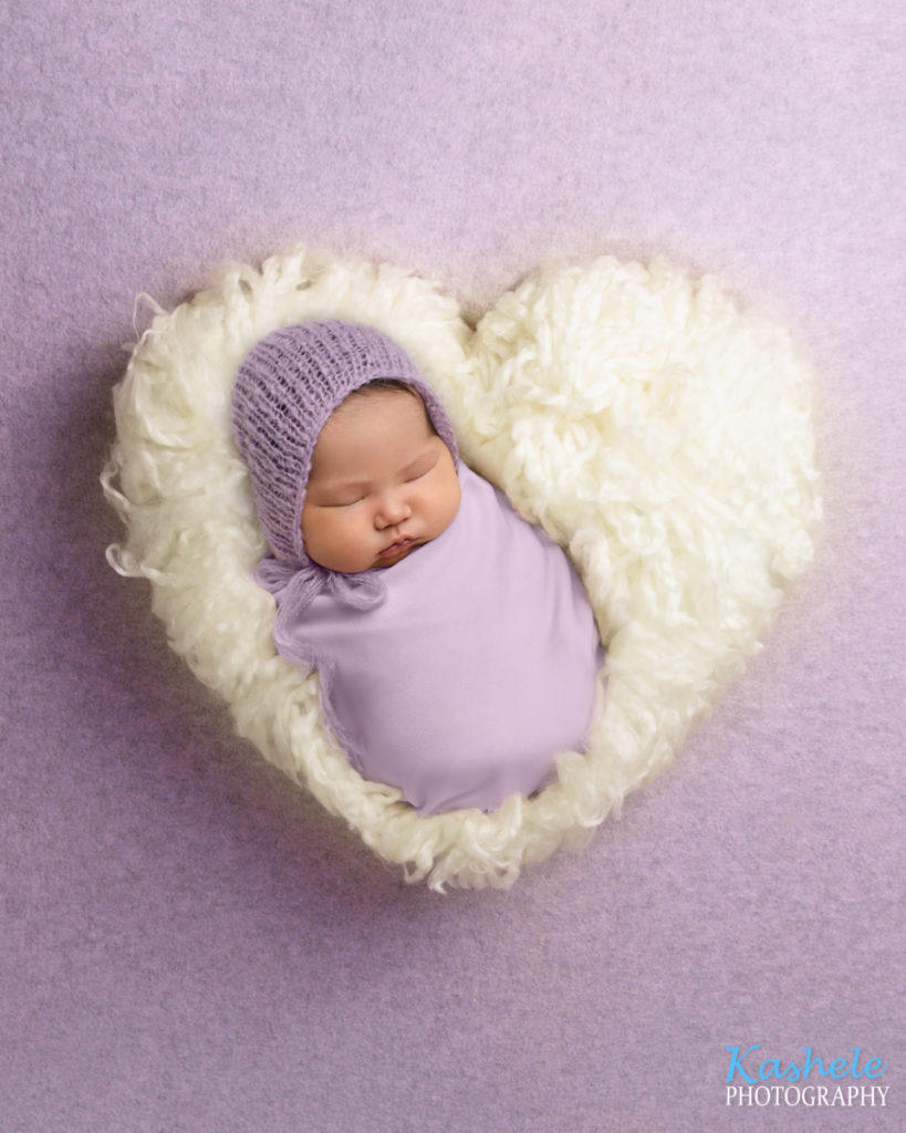 Image of baby swaddled in a heart of fluff