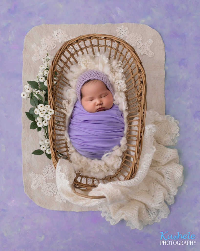 Image of baby girl snuggled in a basket for Eagle Mountain Newborn Photography post