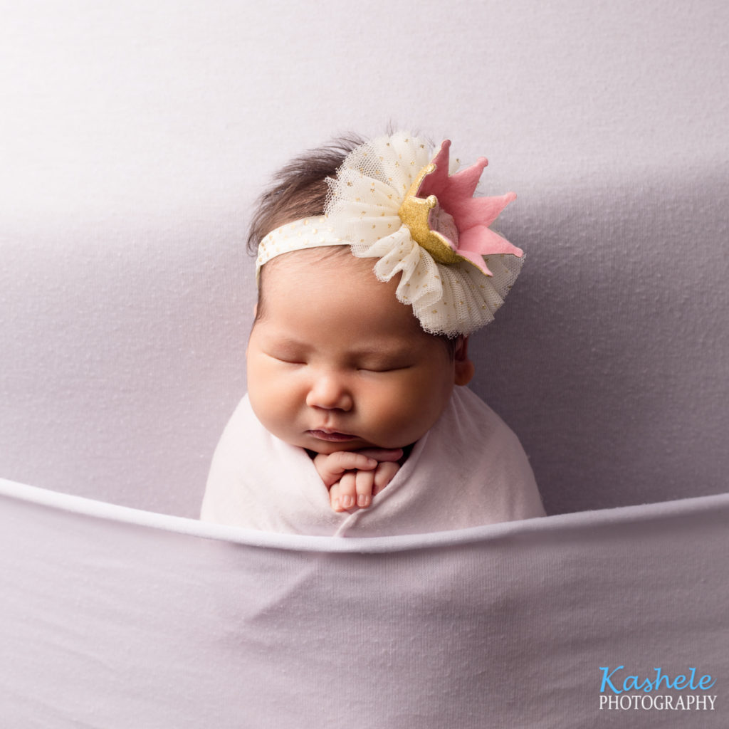 Image of baby girl with a crown tucked into bed