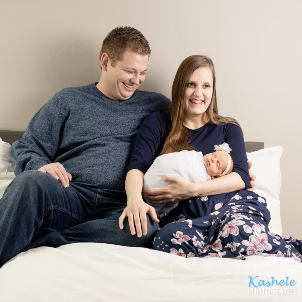 Image of baby girl with Mom and Dad for Logan Newborn Photography post