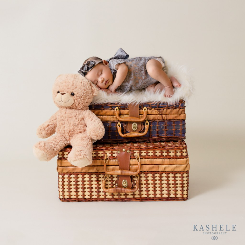 Image of baby resting on top of suitcases with a teddy bear for don't try this at home post