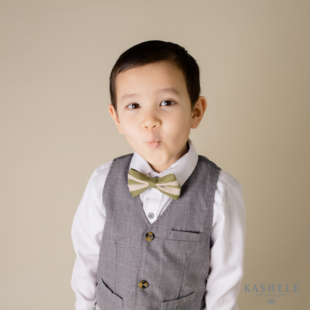 Image of little boy making a kissy face in a St. Pactrick's Day bowtie