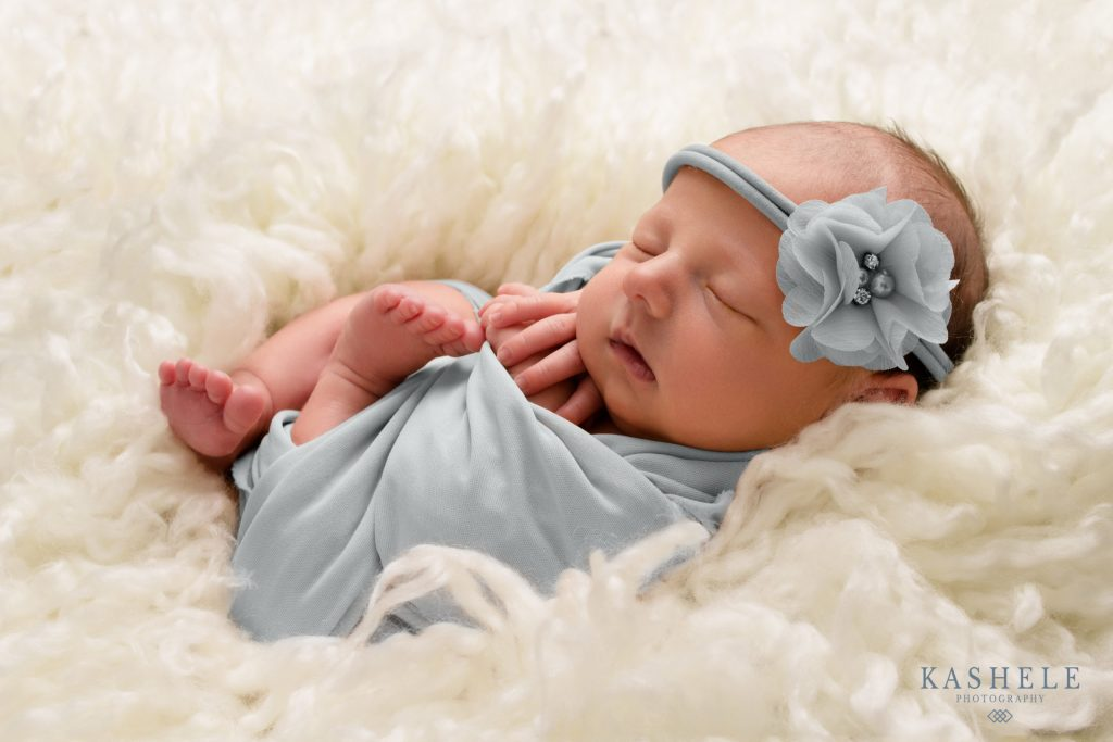 Newborn Photography Utah baby girl wrapped in gray surrounded by white fluff