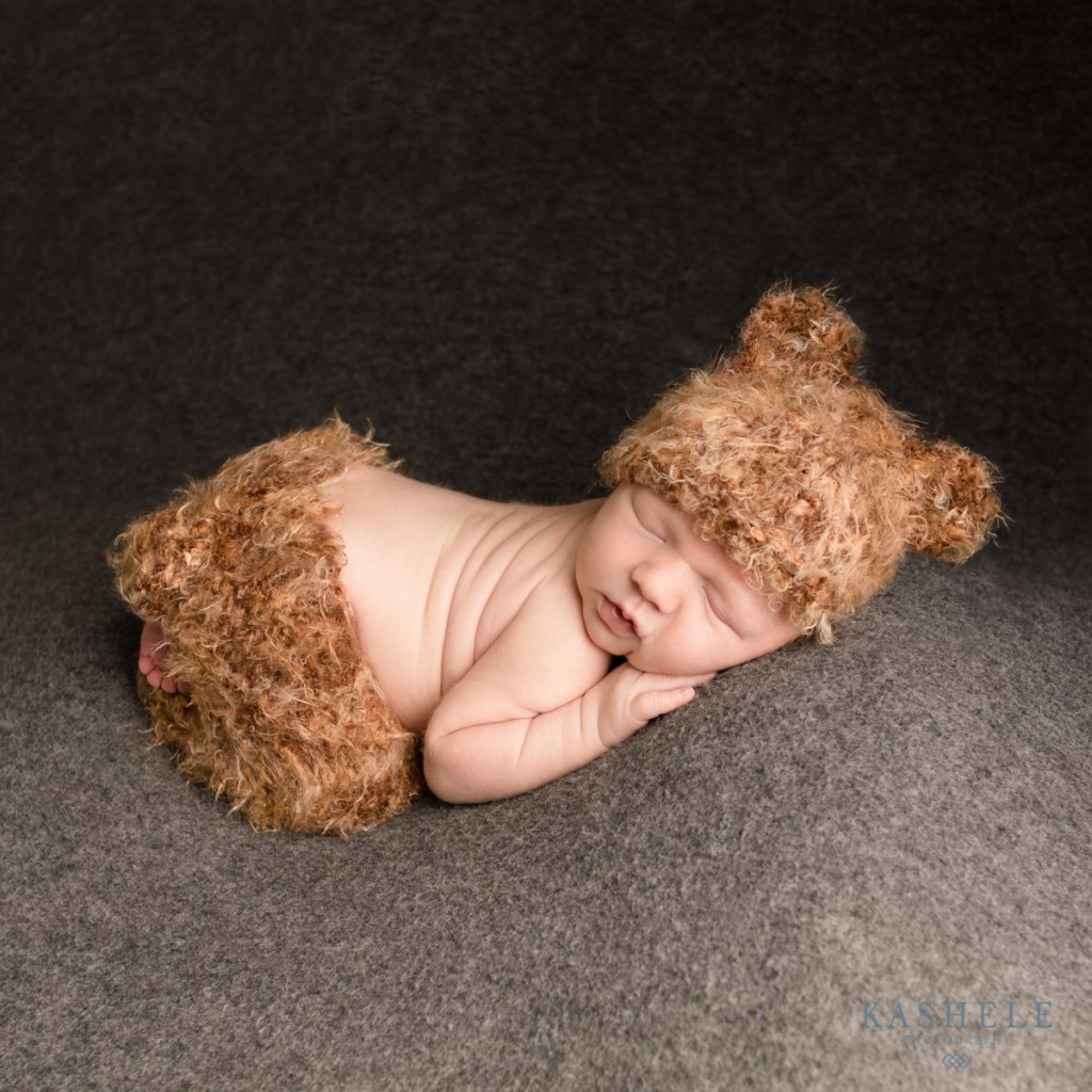 Baby in a bear outfit for Questions to ask your newborn photographer post