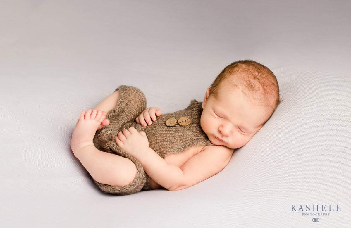 Newborn baby boy in huck finn pose