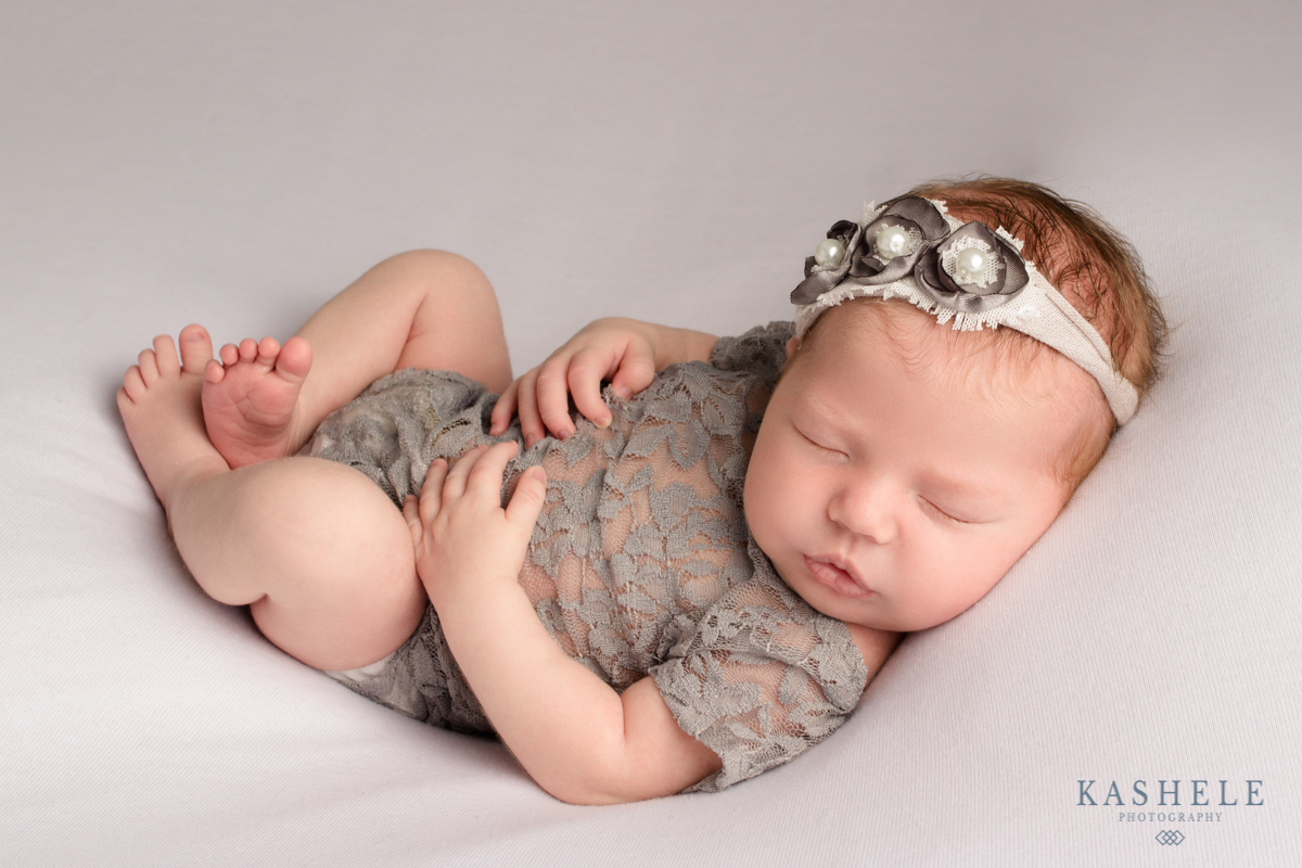 Newborn baby girl in Huck Finn pose for professional newborn photographer post