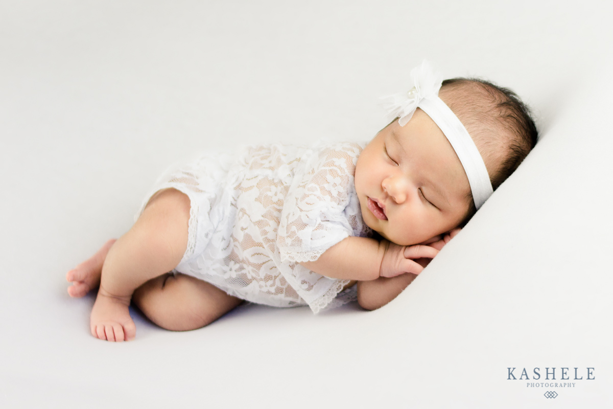 Newborn baby girl in white sleeping on her side for professional newborn photographer post