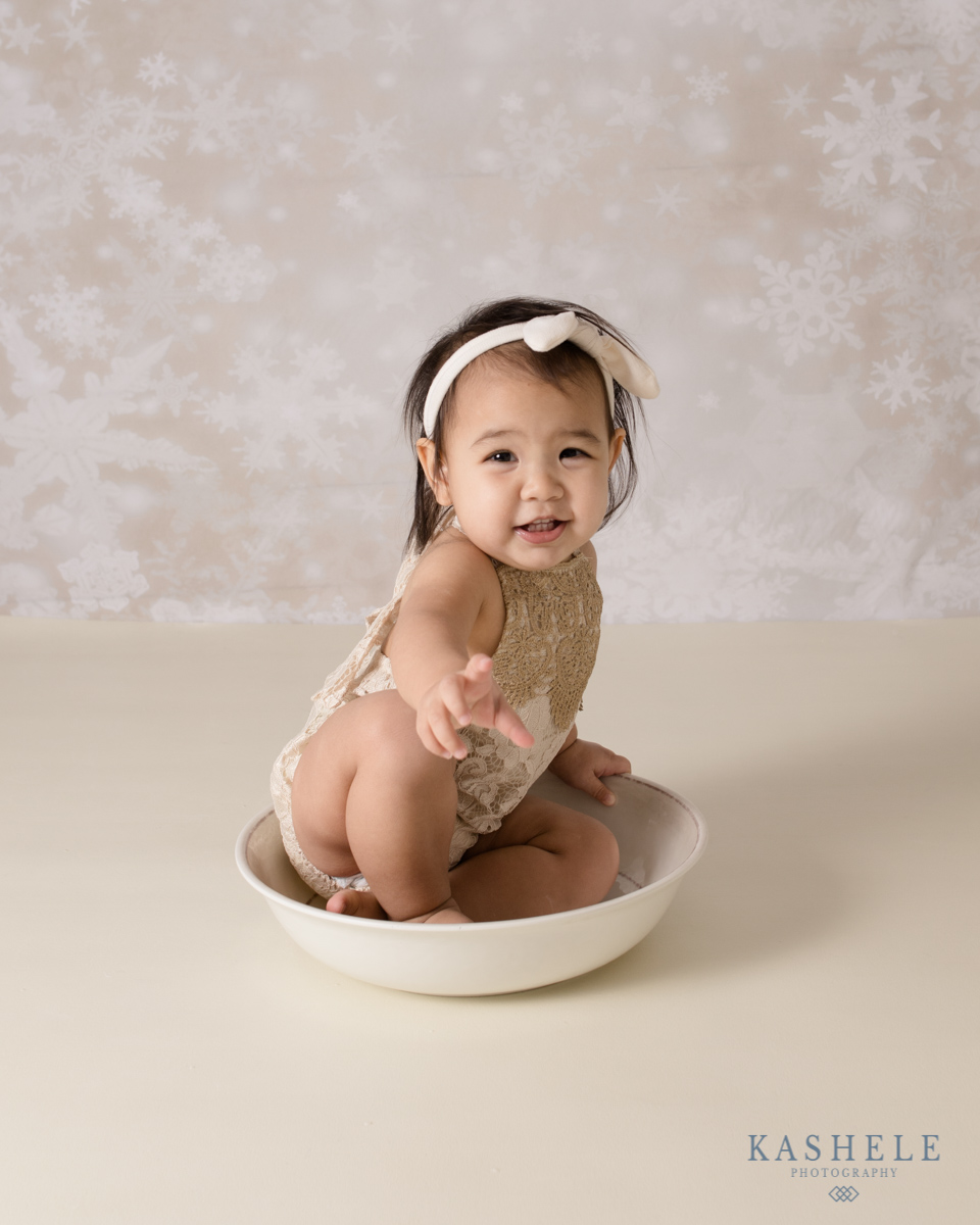 Little girl sitting in bowl for Why Schedule a Milestone Session post