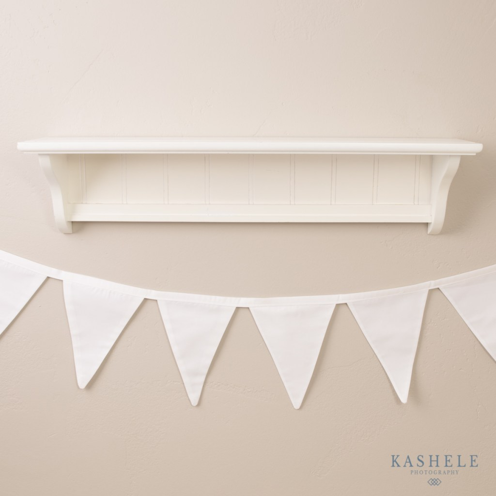 Image of white bunting banner hanging under a shelf