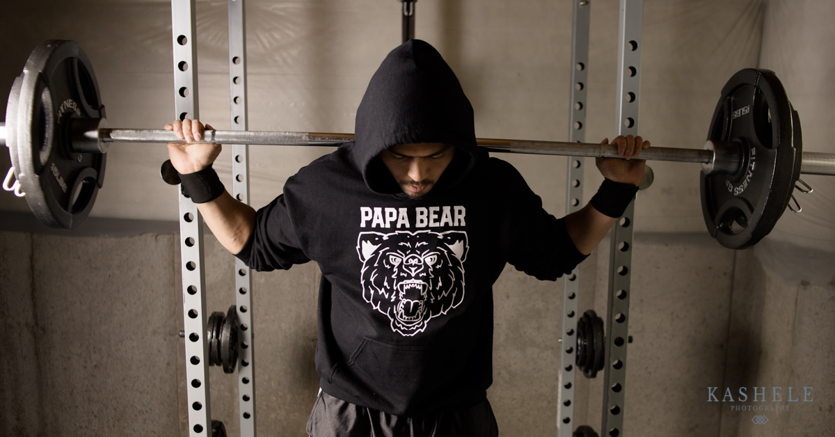 Man lifting weights in papa bear hoodie