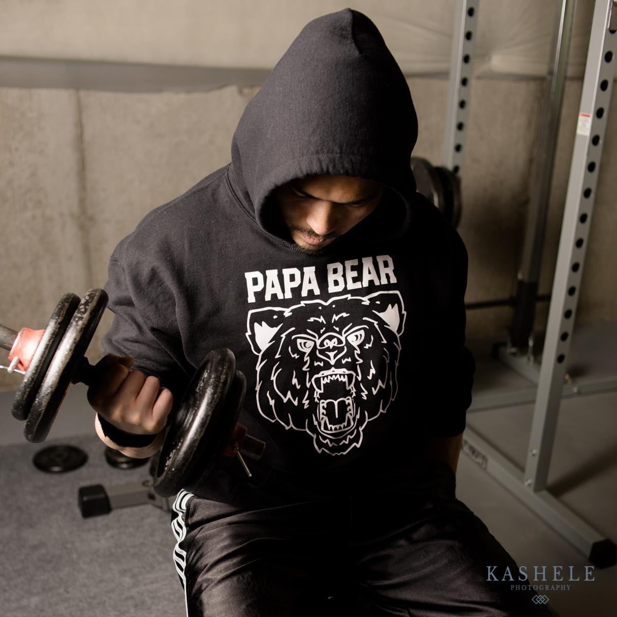 Man doing bicep curl in papa Bear hoodie